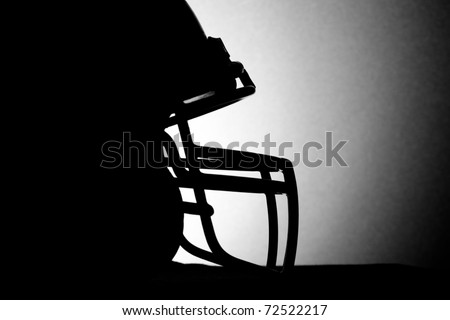 This is a black and white silhouette shot of a football helmet.