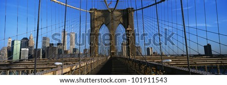 This is a close-up of the Brooklyn Bridge Walkway to Manhattan. The Manhattan skyline is in the background. There is steel fencing is on either side of the bridge.