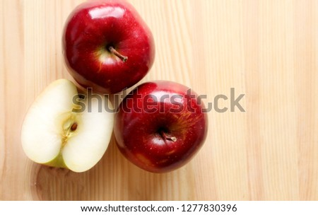 This is a close-up picture of an organic juicy red apple on a wooden surface