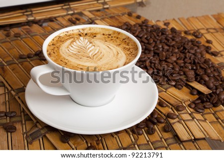 This is a cup of espresso coffee with a pattern on the foam and corn coffee on background.