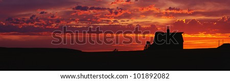 This is a farm at sunset. The farm house is silhouetted against an orange sky. - stock photo