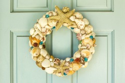 This is a front door  decor for summer with  starfishs , different of shells  ,Molluse shells,seashells,Paw shells, Banded shells and some of flowers and a little glass balls.