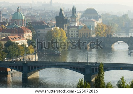 This is a general view of Prague in autumn. Yellow trees flavor the cityscape.