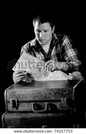 This is a high contrast, black and white image of a young man bent down next to a couple old suitcases looking at a map. Shot with hard light on a black background.