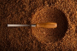 This is a high-quality chisel, with a maple handle, with perfect bevels and grounded surface, photographed on a bed of fresh shavings of an industrial planer. The chips are from oak, beech and walnut.