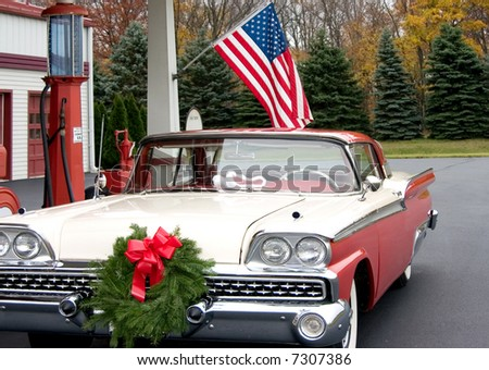 this is a mid 1950s car at a gasoline service station with a wreath on the front of the grill.