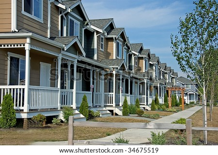 This is a newer neighborhood with a row of beautiful townhouses against a bright blue sky.