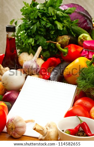 This is a notebook of paper on a background of fresh vegetables. This recipe is delicious and healthy dishes.