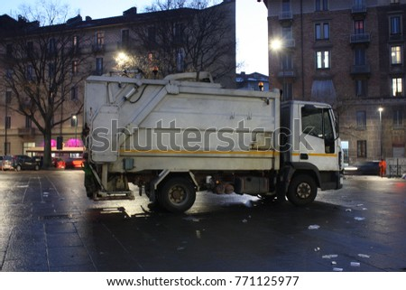 This is a photo of a white garbage truck for picking up trashes all around the town. This truck makes all the city to be clean. It is so useful vehicle.  #771125977