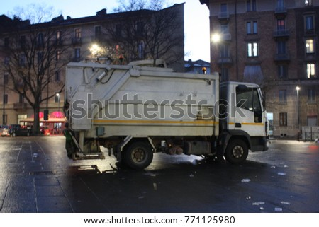 This is a photo of a white garbage truck for picking up trashes all around the town. This truck makes all the city to be clean. It is so useful vehicle.  #771125980