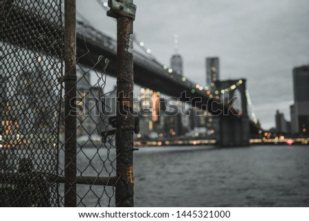 This is a photo of the Brooklyn bridge form Brooklyn. Down Town Manhattan is visible in the background. A fence is focussed giving some context and the rest is unfocussed due to an artistic choice