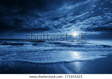 Stock Photo This is a photographic illustration of a beautiful midnight blue ocean moonrise along the coast with dramatic sky and rolling waves.