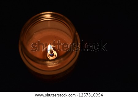 This is a picture of a candle lightning into the darkness in warm tones and focused on the fire.