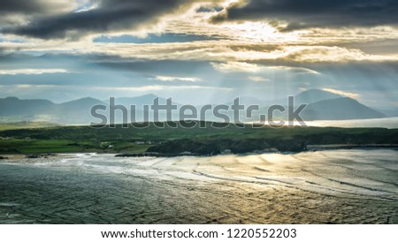 This is a picute of Dough Island in Donegal Ireland.  The sun is peaking through the clouds producing rays of sunlight hitting the ocean and land.