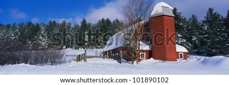 This is a red barn after a newly fallen winter snow storm.