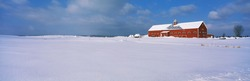 This is a red barn in the snow. It is representative of winter in New England.