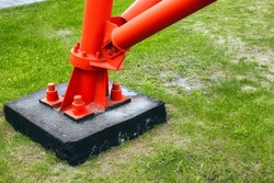 This is a red metal support or pole attached to the concrete base with large anchor bolts and nuts. Reliable and stable construction. Background or screen saver for advertisement of services on