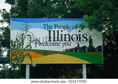 This is a road sign that says, the people of Illinois welcome you. There is a stalk of corn on one side of the sign, and the city skyline of Chicago on the other side. It is set near green trees.