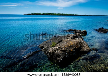 This is a rocky shoreline view from the main island of Isle Royale National Park in Lake Superior off Copper Harbor, Michigan. Outer islands can be seen in the distance.