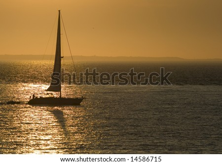 This is a sail boat sailing through a golden reflection