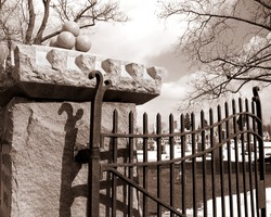 This is a sepia tone of an old iron gate at a cemetery.