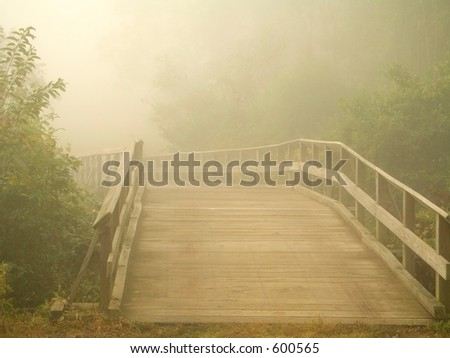 This is a shot of a wooden footbridge early in the morning during a dense fog.