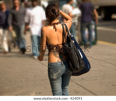 This is a shot of a young lady with several tattoos walking in the city.
