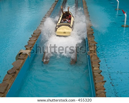 This is a shot of some teenagers getting cooled off on a log flume ride in an amusement park.