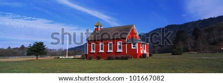 This is a small school house. It is painted a bright red with white trim on the windows. The sky is blue and it is surrounded by green grass, bushes and trees.