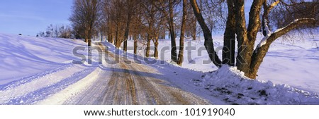This is a snowy road at sunrise. It shows Winter in New England.
