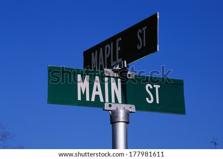 This is a street sign labeling the corner of Main Street & Maple Street. The sign is green with white lettering against a blue sky. #177981611
