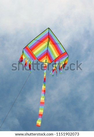 This is a symbol of freedom:  colorful kite flies high in the blue sky #1151902073
