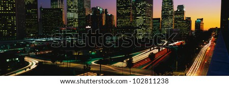 This is a view of the Harbor Freeway in Los Angeles with rush hour traffic at sunset. There are streaked lights from the cars on the freeway.