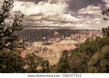 This is a Vintage Landscape View of the Grand Canyon with Clouds, Trees, Green Vegetations and Dramatic Sky in Arizona, USA
