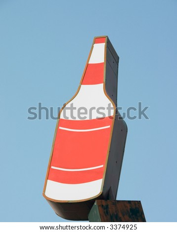This is a vintage sign for a package liquor, party store, isolated against the blue sky.