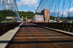 This is a wide view showing the cables and metal grate deck of the historic Wheeling Suspension Bridge that carries the National Road over the Ohio River in Wheeling, West Virginia.