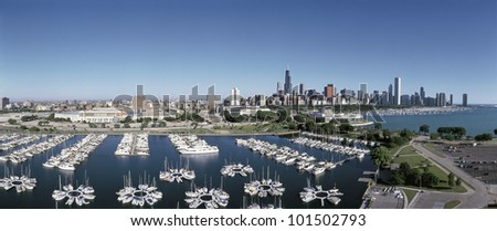 This is an aerial view of the Chicago Harbor and the skyline on Lake Michigan during summer. Boats are moored in the harbor in the foreground.