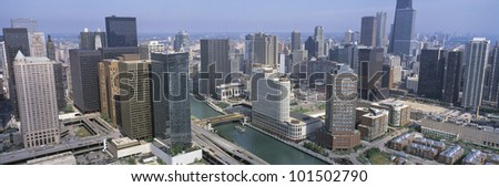 This is an aerial view of the Chicago River and the surrounding skyline in summer.