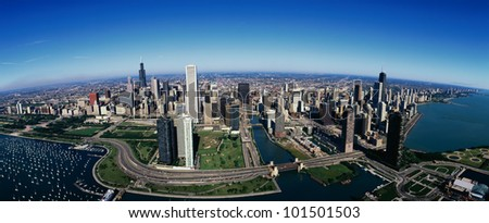 This is an aerial view of the Chicago skyline, Lake Michigan and the Chicago Harbor on left during summer.  Boats are moored in the harbor and Lake Shore Drive winds around the city.