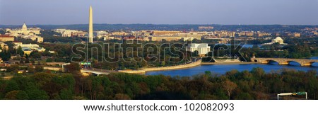 This is an aerial view of Washington, DC. The Potomac River runs through the center with the Key Bridge at right at sunset.