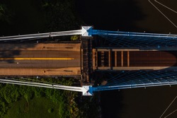 This is an aerial view showing the cables and metal grate bridge deck of the historic Wheeling Suspension Bridge that carries the National Road over the Ohio River in Wheeling, West Virginia.