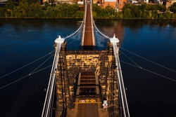 This is an aerial view showing the cables, masonry, and metal grate deck of the historic Wheeling Suspension Bridge that carries the National Road over the Ohio River in Wheeling, West Virginia.