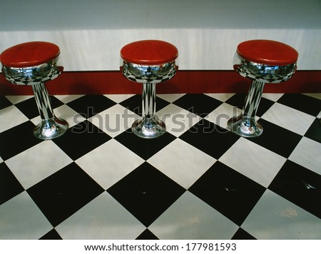 This is an art deco style restaurant. It has a black and white checkerboard tile floor with red vinyl stools next to the counter. It is a typical 50's style diner. Stock photo ©