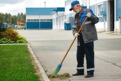 This is an elderly janitor with a broom in a medical mask on the street sweeping the territory. An old man in a work uniform works during a time of pandemic and unemployment.