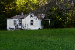 This is an exterior view of an abandoned white painted house in rural Virginia.