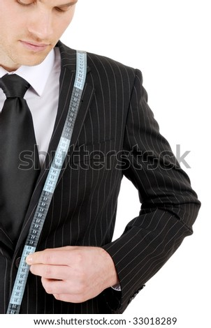 This is an image of business man using a tape measure to measure across his suit.