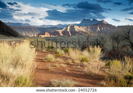 This is an image of mountains and rock formations outside of Zion Canyon as the light fades before sunset. - stock photo