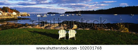 This is an image of two white lawn chairs facing toward the nearby harbor.