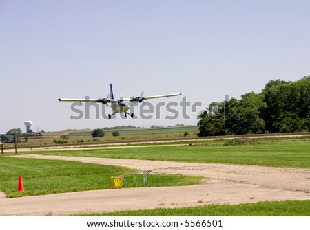 This is an medium sized twin engine plane landing on a grass landing strip.