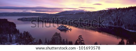 This is Emerald Bay at sunrise after a winter snow storm. There is snow on the land surrounding the bay.